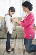 Mother buttoning daughter's sweater in living room Stock Photos
