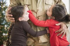 Daughters hugging soldier father Stock Photos