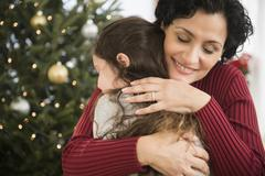 Mother and daughter hugging by Christmas tree Stock Photos