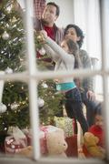 Family decorating Christmas tree together Stock Photos