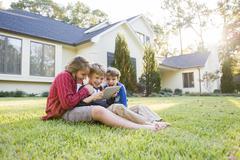 Caucasian boys using digital tablet on lawn Stock Photos