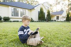 Caucasian boy using digital tablet on lawn Stock Photos