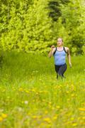 Caucasian woman running in tall grass Stock Photos