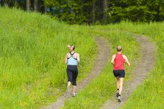 Caucasian women running on path Stock Photos