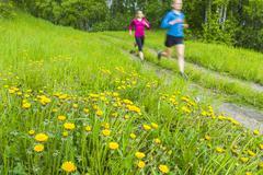 Caucasian women running on path - stock photo