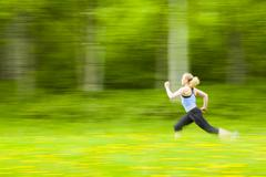 Blurred view of Caucasian woman running in tall grass - stock photo