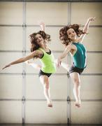 Dancers leaping in studio - stock photo
