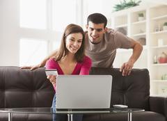 Couple shopping online on sofa - stock photo