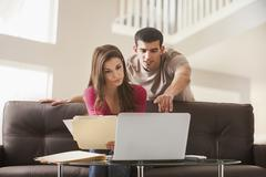Couple reading papers at laptop together - stock photo