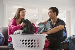 Couple sorting laundry together Stock Photos