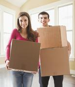 Couple carrying cardboard boxes in new home - stock photo