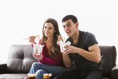 Couple eating Chinese food on sofa Stock Photos