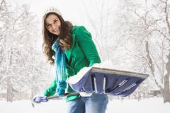 Caucasian woman shoveling snow outdoors Stock Photos