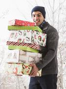 Hispanic man holding Christmas gifts in snow - stock photo