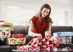 Caucasian woman wrapping Christmas presents in living room Stock Photos