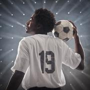 Black soccer player holding ball Stock Photos