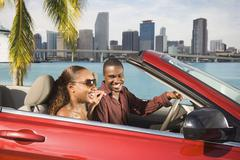 African American couple driving in convertible - stock photo