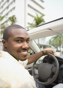 African American man driving convertible - stock photo
