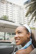 Mixed race woman riding in convertible - stock photo