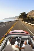 Couple driving convertible on coastal road - stock photo