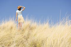 Stock Photo of Caucasian woman walking in tall grass