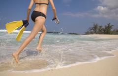 Stock Photo of Caucasian woman carrying scuba equipment to water
