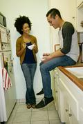 Mixed race couple relaxing in kitchen Stock Photos