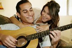 Man playing guitar for girlfriend - stock photo