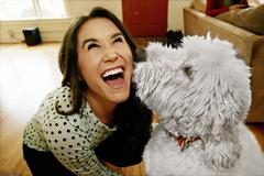 Dog licking Caucasian woman's face - stock photo