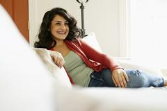 Middle Eastern woman relaxing on sofa Stock Photos