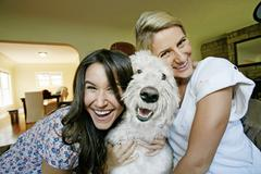 Women petting dog in kitchen - stock photo