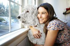 Caucasian woman hugging dog at window Stock Photos