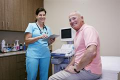 Caucasian nurse and patient smiling in office - stock photo