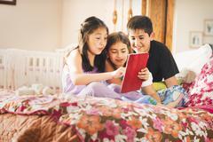 Lapset käyttämällä digitaalista tabletti yhdessä Kuvituskuvat