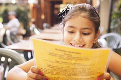 Mixed race girl reading menu in restaurant - stock photo