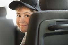 Hispanic boy smiling in car - stock photo
