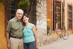 Hispanic couple smiling on city street Stock Photos