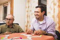 Hispanic men playing dominoes at table Stock Photos