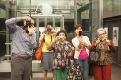 Tourists taking pictures in museum - stock photo