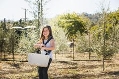 Caucasian girl carrying basket in olive grove Stock Photos
