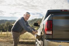 Older Caucasian man tying his shoe on truck wheel - stock photo