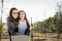 Caucasian mother and daughter smiling in olive grove - stock photo