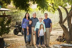 Family smiling in olive grove - stock photo