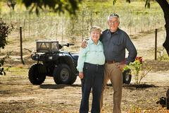 Older Caucasian couple smiling in olive grove - stock photo