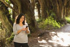 Hispanic woman using cell phone outdoors Stock Photos