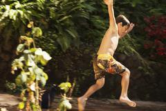 Mixed race boy jumping Stock Photos