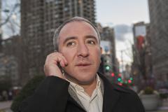 Hispanic businessman talking on cell phone on city street Stock Photos