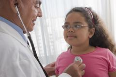 Hispanic doctor checking patient's heartbeat Stock Photos