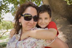 Hispanic mother carrying son piggyback - stock photo