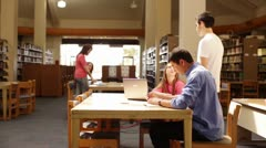 University students talking in the library central table Stock Footage